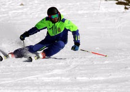 A Skier glides down the piste in a sporty way and take the bend within the framework of the Private Ski Lessons for Adults - All levels with the ski school Escuela Española de Esquí Panticosa.