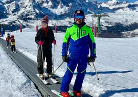 A participant of ski lessons for adults - beginner stands at the conveyor belt together with a ski instructor of the ski school Escuela Española de Esquí Panticosa.
