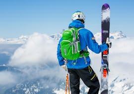 Un skieur tient ses skis tandis qu'il profite de la vue sur le paysage pendant son cours particulier de ski adultes - chamonix - tous niveaux avec l'école de ski Freedom Snowsports.