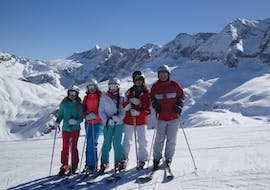 Children stand on a sunny day on the white piste and laugh into the camera during the kids ski lessons (6-14 years) - beginner from the ski school Escuela Española de Esquí Panticosa.