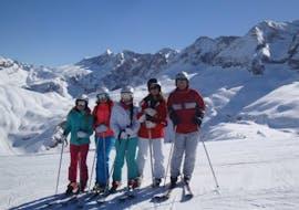 Los niños están parados en un día soleado en la pista blanca y sonríen en la cámara durante las clases de esquí para niños (6-14 años) - principiantes de la Escuela Española de Esquí Panticosa.