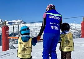 Children hold the hand of their ski instructor and look towards the mountains within the framework of the Private Ski Lessons for Kids (3-14 years) - All levels with the ski school Escuela Española de Esquí Panticosa.