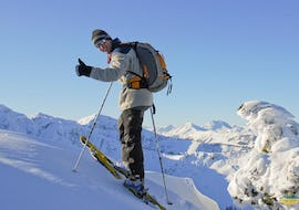 A skier happily climbs the mountain and smiles proudly into the camera with the private and groups ski touring guide Kitzbühel - All Ages of the ski school Motion Center Lofer.