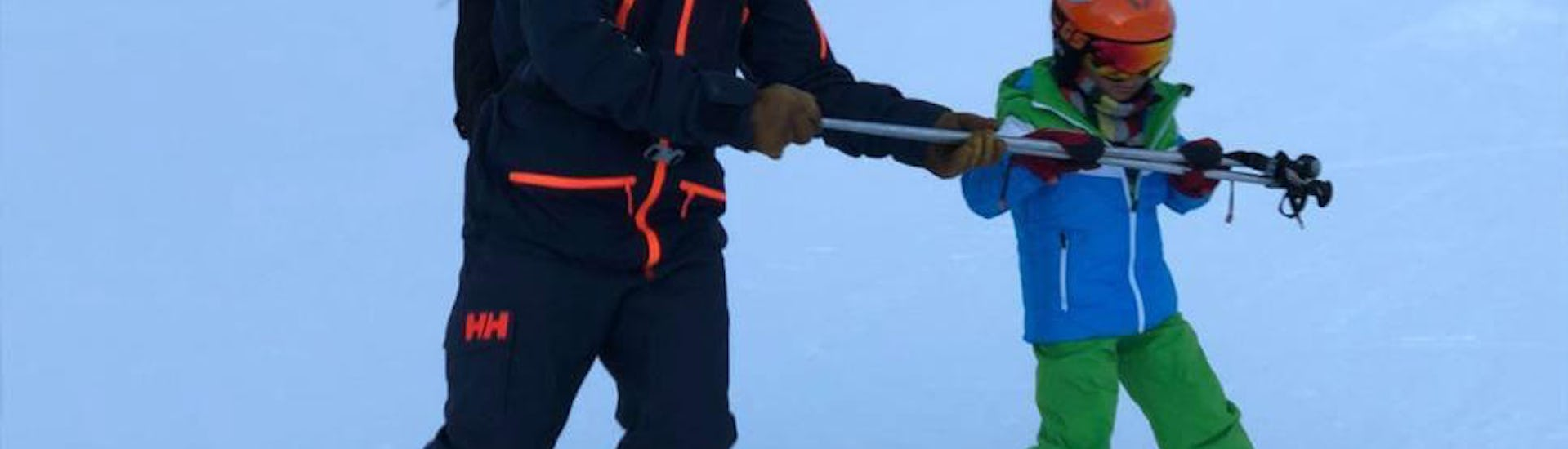 Ski instructor shows the child how to hold the ski sticks correctly during Private Ski Lessons for Kids - Megève - All Ages with the ski school Skibex.