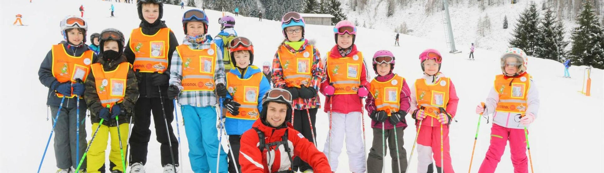 """A group of children and their ski instructor from S4 Snowsport Fieberbrunn are smiling at the camera during their Kids Ski Lessons """"Tatzis Skicircus"""" (3-14 years)."""