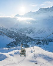 An image of the gondola carrying skiers up to the top of the mountain in Breuil-Cervinia, a popular ski resort for booking ski lessons with one of the local ski schools.