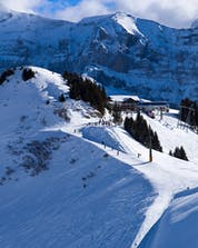 An image of the ski slopes of Croix de Culet in the Swiss ski resort of Champéry, a popular place amongst visitors who want to learn to ski by taking ski lessons with one of the local ski schools.