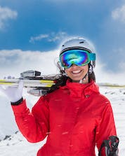 An image of a young woman carrying her skis in La Molina/Masella, a popular place to book ski lessons with one of the local ski schools.