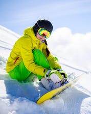 A female snowboarder is sitting on one of the ski slopes in Schönried-Saanenmöser-Zweisimmen, where local ski schools take their students for their ski lessons.