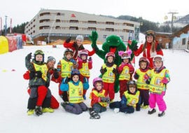 """The children sit together with the mascot and the ski instructor of the ski school S4 Snowsports Fieberbrunn in the snow and raise their hands during the kids ski lessons """"Tatzis Skicircus"""" (3-14 years) - All Levels."""