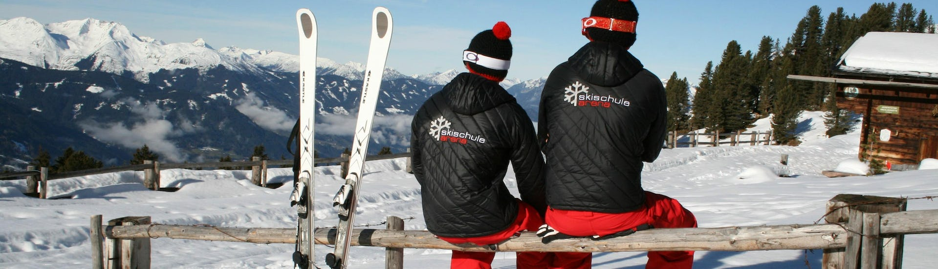 Two ski instructors from the ski school Skischule Arena in Zell am Ziller are preched on a wooden fence, looking out over the beautiful mountain scenery of the Zillertal Valley.