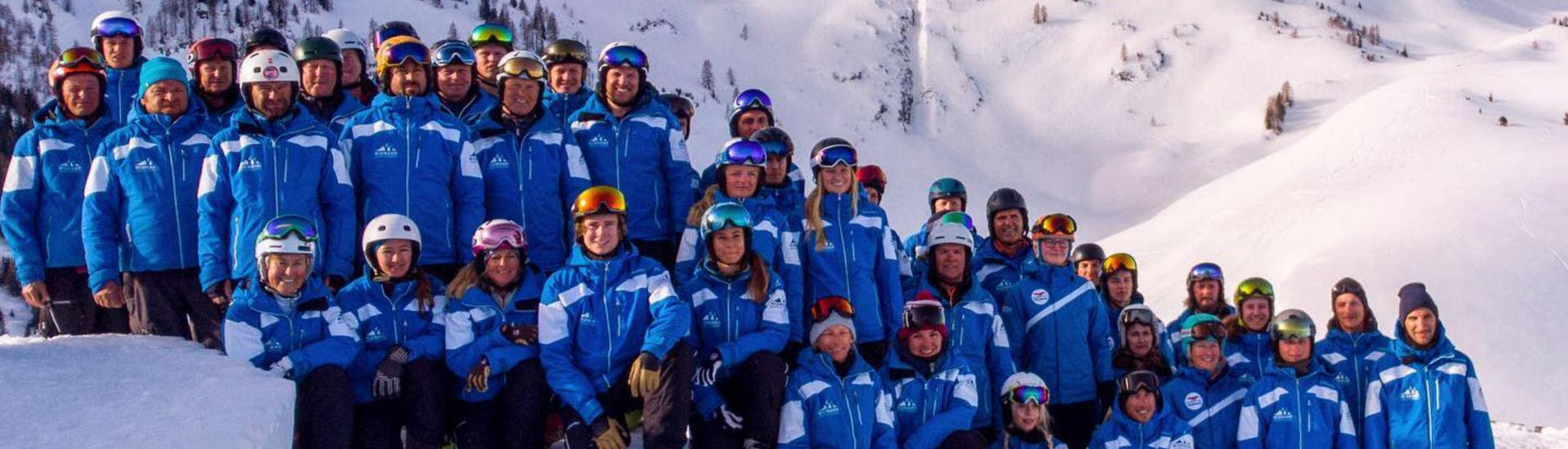 The ski instructors from the ski school Skischule Fieberbrunn Widmann Mountain Sports are collectively posing for a group photo in the Tyrolean ski resort of Fieberbrunn.