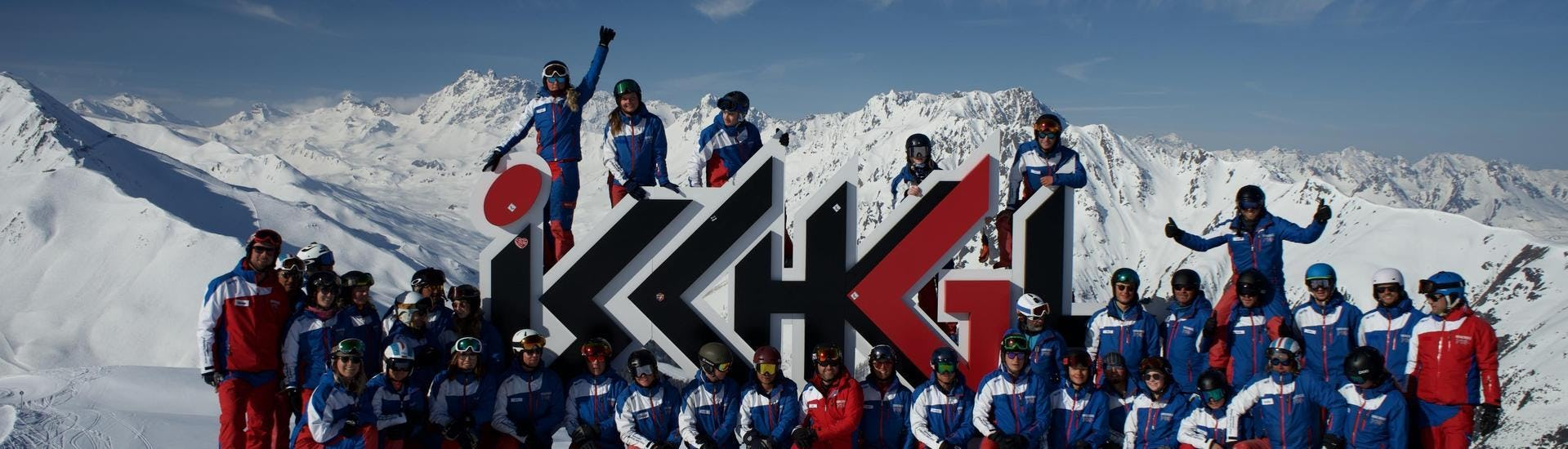 The ski instructors from Skischule Ischgl Schneesport Akademie are gathered around the logo of the ski school and are seemingly looking forward to teaching their ski lessons.
