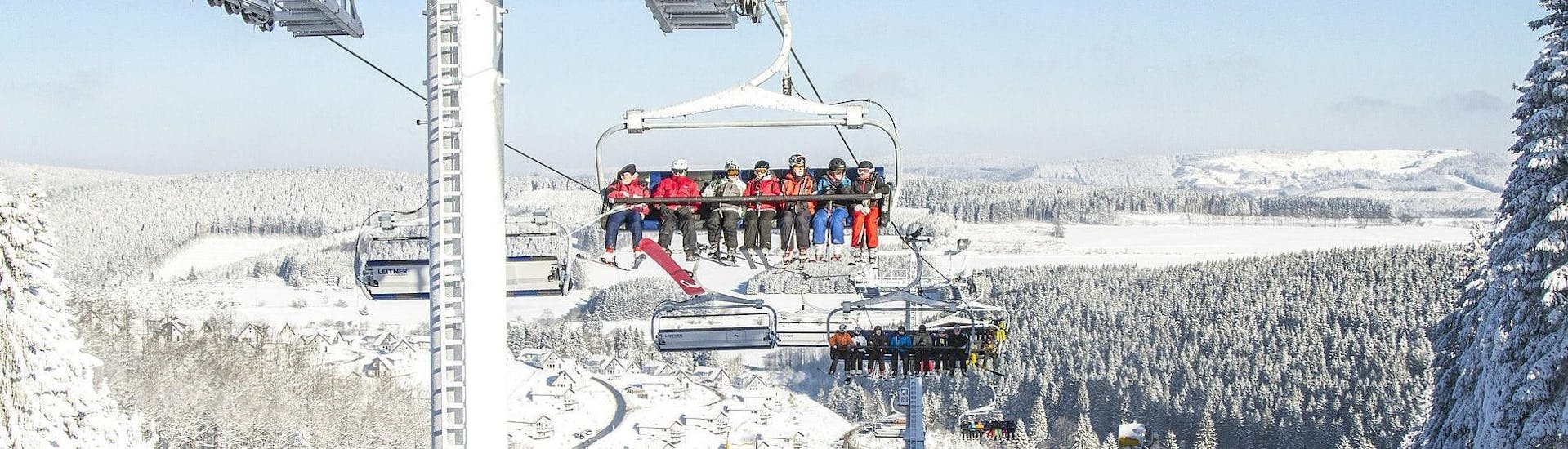 A group of skiers taking a chair lift to the top of a mountain to start one of their ski lessons with Skischule Kahler Asten in the ski resort of Winterberg.