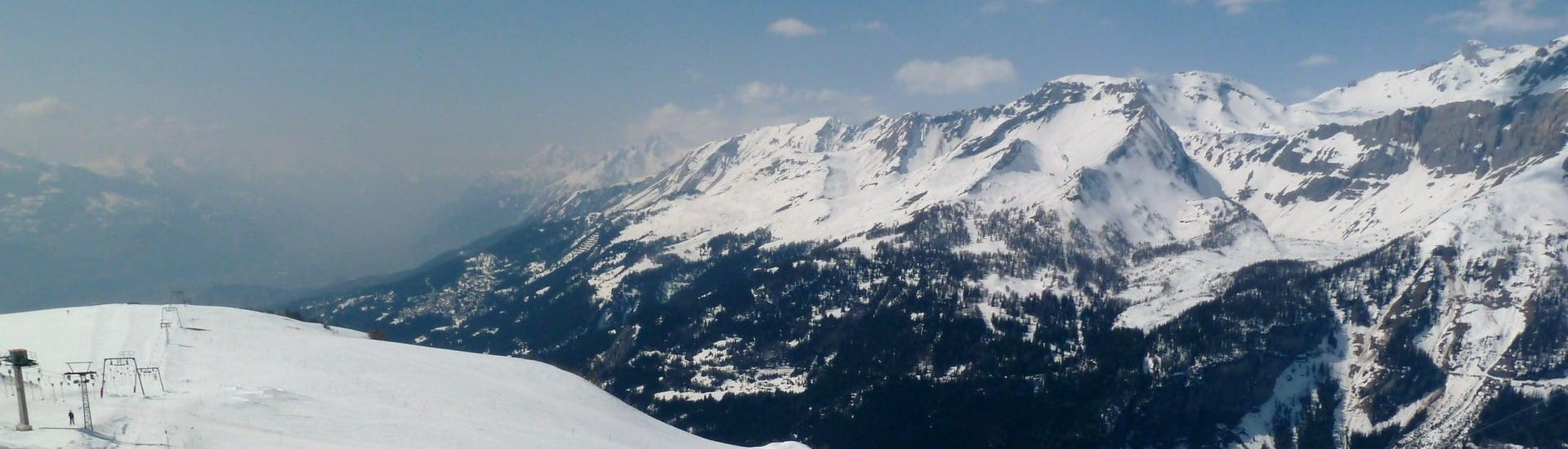View over the sunny mountain landscape while learning to ski with the ski schools in Crans-Montana.