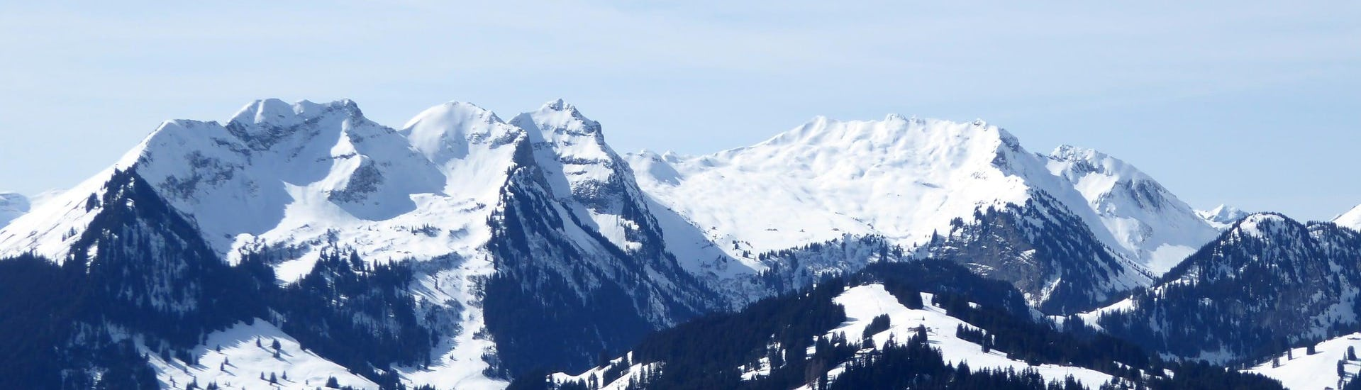 View over the sunny mountain landscape while learning to ski with the ski schools in Gstaad-Saanen.