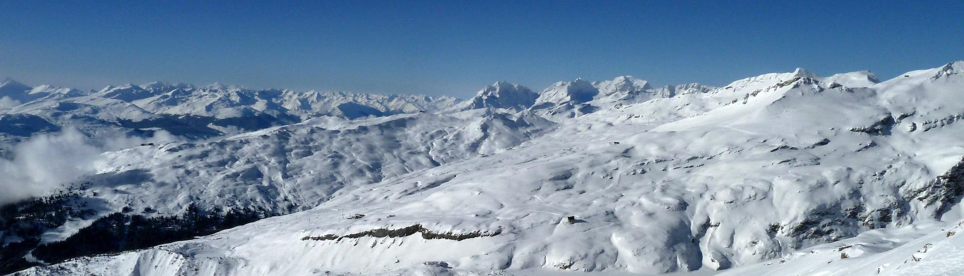 View over the sunny mountain landscape while learning to ski with the ski schools in Laax-Flims-Falera.