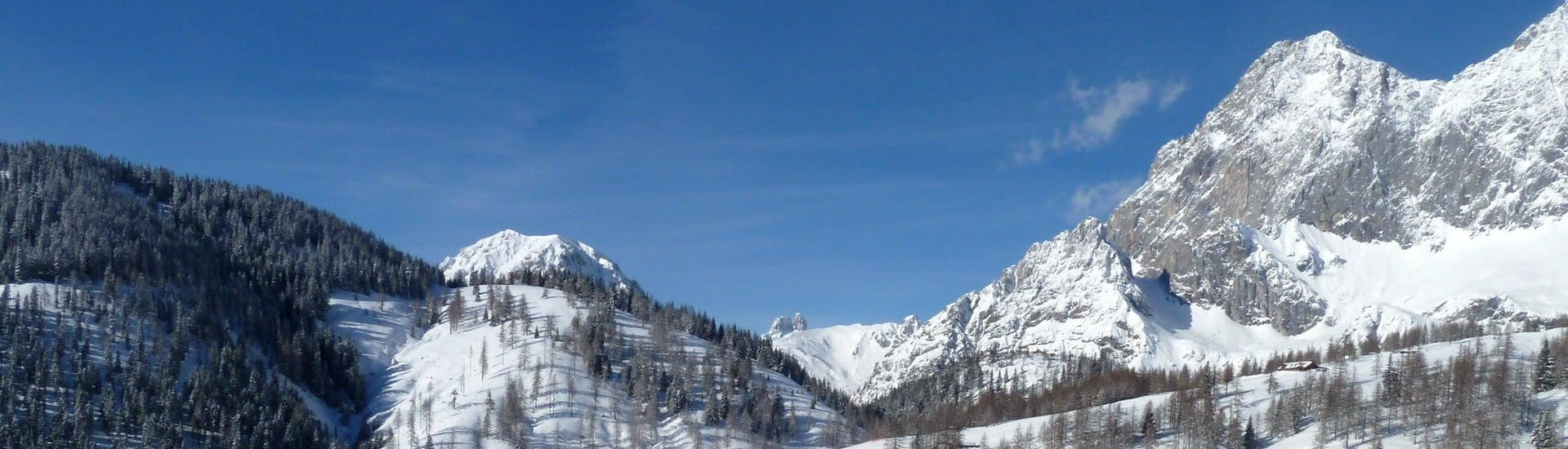 View over the sunny mountain landscape while learning to ski with the ski schools in Ramsau am Dachstein.