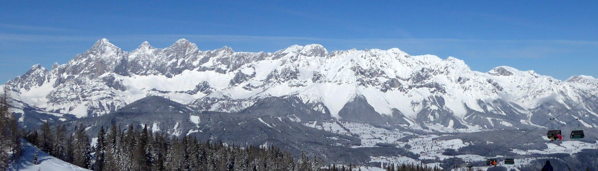 View over the sunny mountain landscape while learning to ski with the ski schools in Reiteralm.