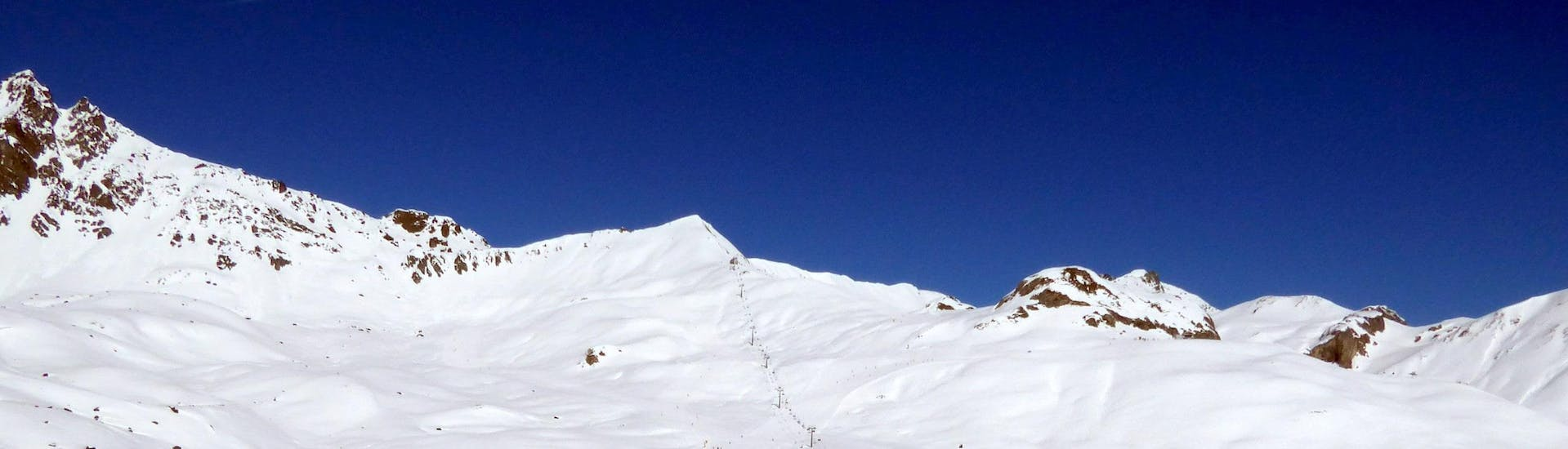 View over the sunny mountain landscape while learning to ski with the ski schools in Samnaun.