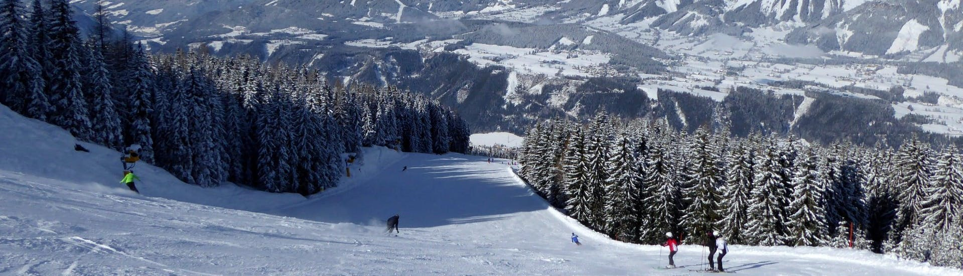 Vue sur un paysage de montagne ensoleillé lors d'un cours de ski avec l'une des écoles de ski de la station de ski Schladming-Planai.