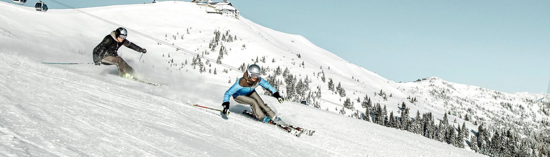 Two skiers are skiing down the ski slopes of the Schmittenhöhe mountain in Zell am See, a popular Austrian ski resort where local ski schools offer ski lessons to all those who want to learn to ski.