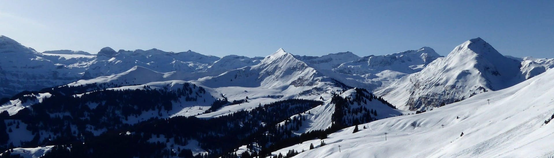 View over the sunny mountain landscape while learning to ski with the ski schools in Schönried-Saanenmöser-Zweisimmen.