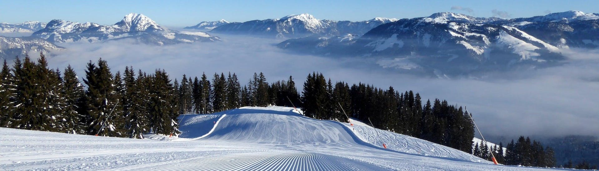 View over the sunny mountain landscape while learning to ski with the ski schools in St. Johann in Tirol.