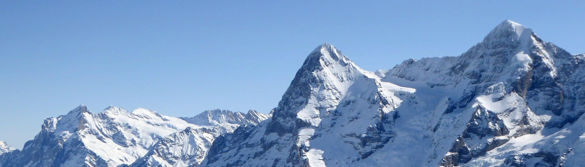 View over the sunny mountain landscape while learning to ski with the ski schools in Wengen.