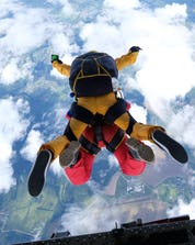 A tandem master and his student are pictured in the moment they jump from the plane while skydiving in Normandy.