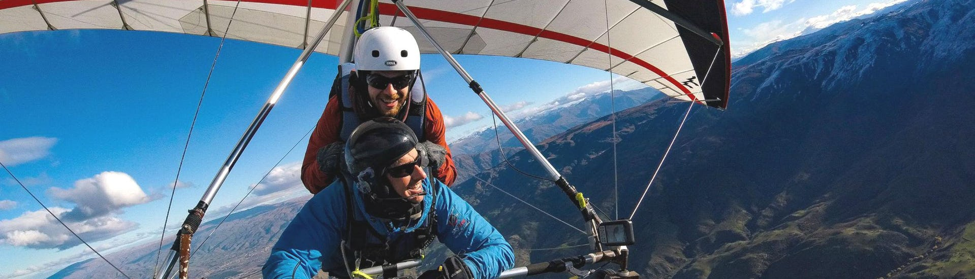 A hang gliding instructor from Skytrek Queenstown and his passenger are enjoying a scenic flight over the beautiful landscape close to Queenstown, New Zealand.