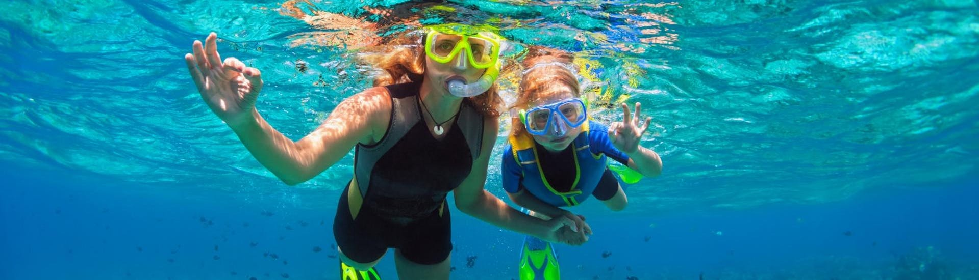 Mother and daughter snorkeling together and having fun underwater
