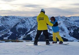"""The snowboard instructor stands on the mountain together with his course participant and explains the correct technique to him as part of the offer """"Private snowboarding lessons for kids and adults - beginners"""" of the snowboard school BOARD.AT."""