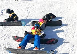 Snowboarders are lying on the snow, tired after all the learning they did during their Snowboarding Lessons (from 10y.) for All Levels - Low Season with the ski school ESF Aussois.