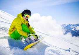 Snowboarder sitting in powder slopes