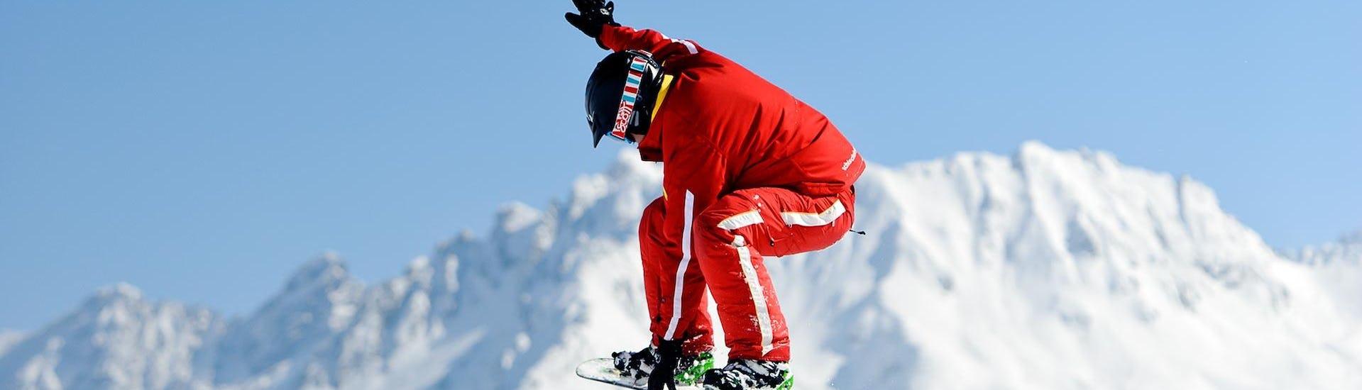Snowboarfahrer springt auf Piste im Snowboardkurs für Kinder & Erwachsene - Fortgeschritten