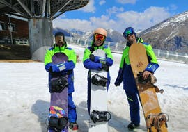 Snowboarders are standing at the exit of the cable car and hold their snowboard within the framework of the offer Private snowboarding lessons for kids and adults - All levels with the ski school Escuela Española de Esquí Panticosa.