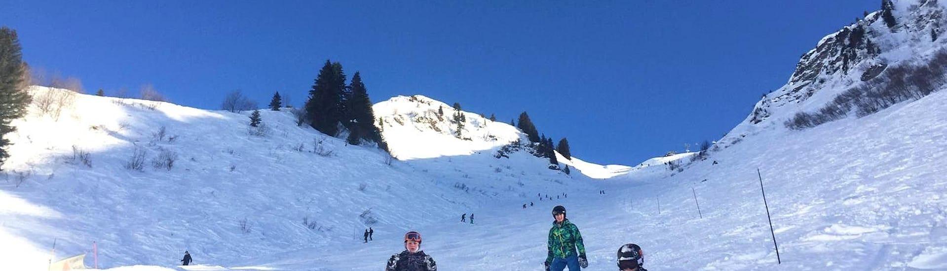 Trois snowboardeurs sont au milieu d'une piste enneigée pendant leur Cours de snowboard - Tous âges - Matin - Haute saison avec l'école de ski ESI Easy2Ride Morzine.