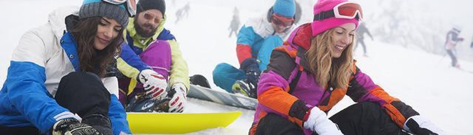 A group of snowboarders are sitting in the snow, fixing their boards to their feet before their Snowboarding Lessons for Kids & Adults -Morning - Low Season with the ski school ESI Easy2Ride Morzine.
