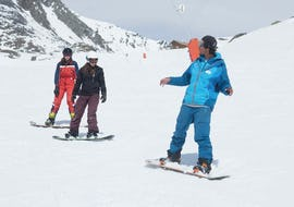 Two young snowboarders follow their instructor from the ski school Ski Cool Val Thorens during Snowboarding Lessons for All Ages - Afternoon - Beginners.