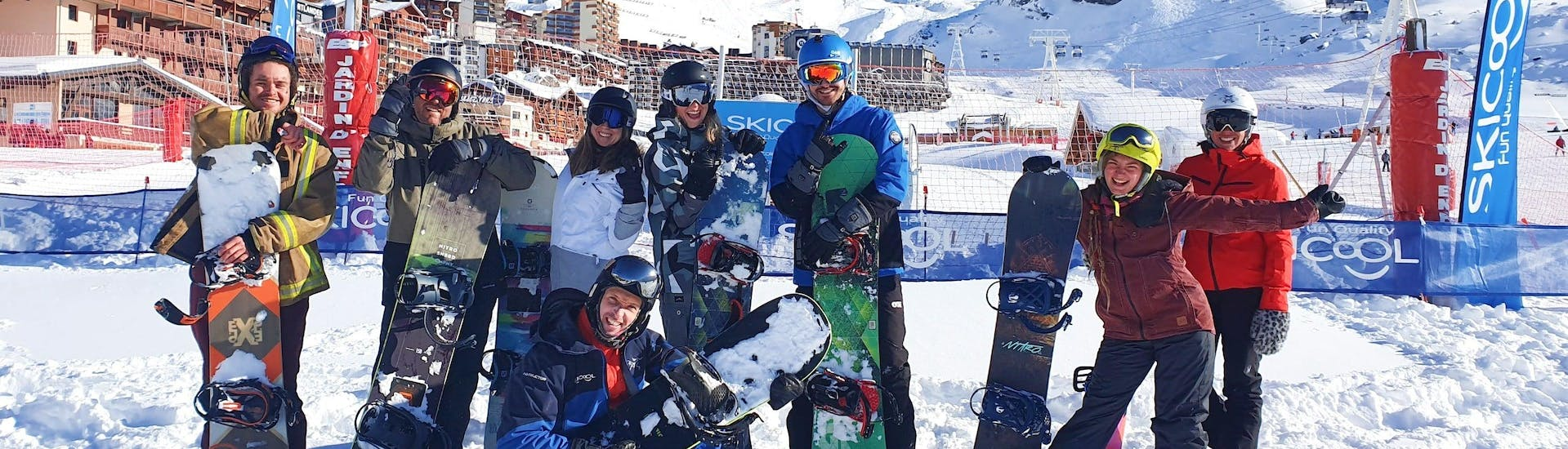 Snowboarders are posing in front of the resort of Val Thorens at the end of their Snowboarding Lessons (from 8 y.) - Morning with Ski Cool Val Thorens.