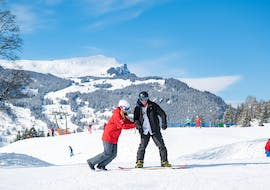 A snowboarding instructor from Outdoor Interlaken is helping one of her students find his balance on the board during his adult snowboarding lessons for beginners with pick-up in Interlaken.