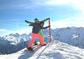 Eine Snowboarderin genießt mit ihrem Lehrer der Alpin Skischule Oberstdorf die unglaubliche Aussicht während dem Snowboardkurs für Erwachsene - Alle Levels.