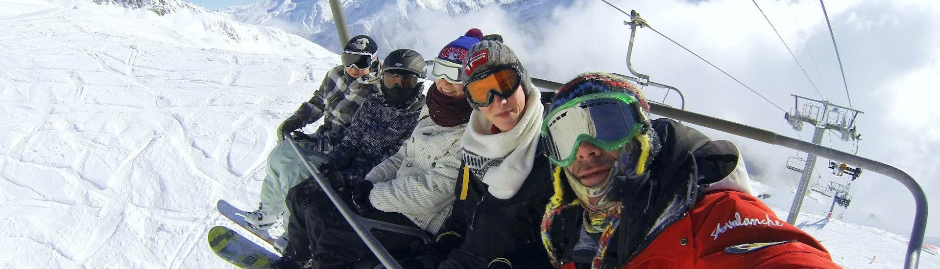 A group of snowboarders is sitting in a chairlift bringing them to the top of the mountain where they will start their Snowboarding Lessons for Adults - All Levels with the ESF Chamonix.