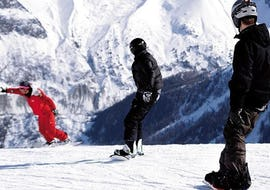 A snowboarder is following their instructor from the ski school ESF Chamonix on a snowy slope during their Snowboarding Lessons for Adults - All Levels.