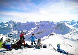 Snowboarder und Snowboarderinnen genießen die spektakuläre Aussicht während dem Snowboardkurs für Erwachsene - Alle Levels, den die Out of Bounds Snowboard School organisiert.