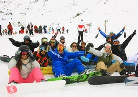 A group of snowboarders is sitting in the snow surrounding their snowboard instructor from the ski school Prosneige Méribel during their Snowboarding Lessons for Adults - All Levels.