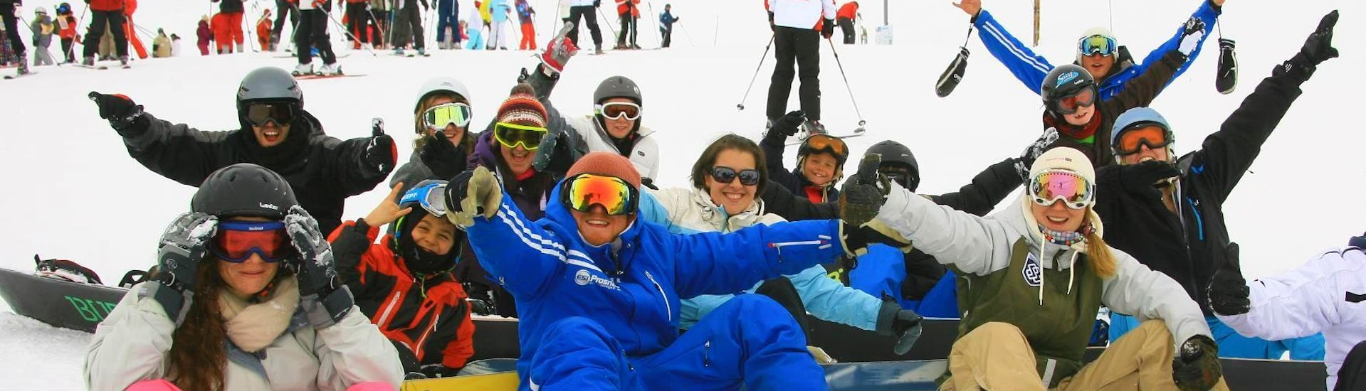 A group of snowboarders is sitting in the snow surrounding their snowboard instructor from the ski school Prosneige Méribel during theirSnowboarding Lessons for Adults - All Levels.