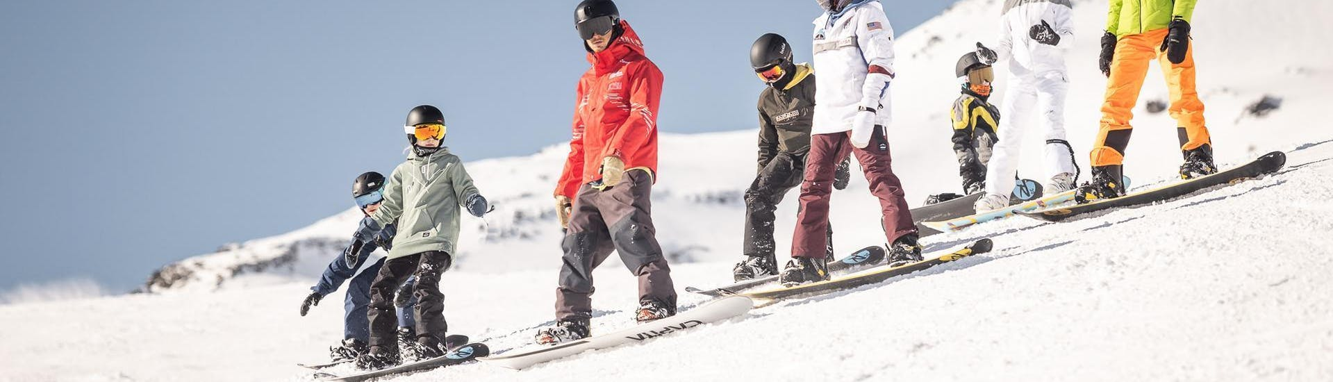 A group of snowboarders is learning how to move on the board during the Snowboarding Lessons for Adults - All Levels organized by the ski school Ski & Snowboardschool Vacancia in the ski resort of Sölden.
