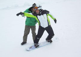 A man is practicing snowboard with an instructor during the Snowboarding Lessons for Kids & Adults - Weekend Special in the Schneesportschule Black Forest Magic Feldberg.